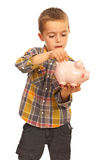 Boy saving money to piggybank Royalty Free Stock Image