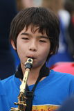 A boy and the saxophone. An asian boy plays the saxophone while marching in a parade Stock Image
