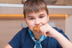 Boy of school age eats bread cake at home. Breakfast, snack, foo. Boy of school age eats bread cake at home. Breakfast, snack and food theme royalty free stock photos