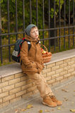 Boy with a school backpack with a basket of apples Stock Photos