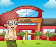 A boy with a school building at his back Royalty Free Stock Image