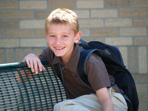 Boy at school bus stop. Young boy waiting on a bench for the school bus Royalty Free Stock Photos