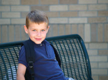 Boy at school bus stop stock photo