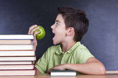 Boy in school desk eating fruit Royalty Free Stock Photos