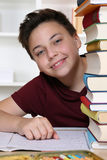 Boy at school looking behind books Royalty Free Stock Image