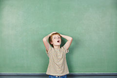 Boy in school putting hands over head Royalty Free Stock Images