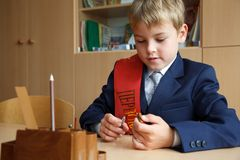 Boy in school uniform at his desk, pen in hand. Royalty Free Stock Photo