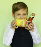 Boy in school uniform and lunch box with sandwich and fruits. Healthy eating Royalty Free Stock Photos