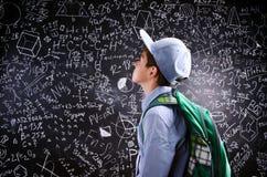 Boy  with schoolbag against big blackboard with mathematical sym Stock Photo