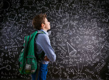 Boy  with schoolbag against big blackboard with mathematical sym Royalty Free Stock Images