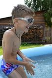 A boy-schoolboy is bathed in the summer during a vacation in a h. Ome inflatable pool with clear blue water in the yard of the house against the background of a stock image