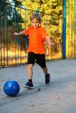 Boy schoolboy playing football on the Playground stock images