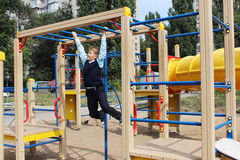 Boy, schoolboy playing on the playground. A boy, a schoolboy playing in a playground in an autumn park, he did not go to school. September, autumn, warmth on the Royalty Free Stock Photos
