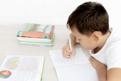 Boy schoolboy teaches lessons writing in notebook and reading books. Nibbling pen on white isolated background stock image