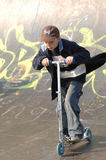 Boy on Scooter. Young male riding two wheeled scooter on graffiti sprayed skate ramp stock image