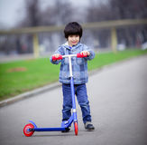 Boy with scooter. A boy with a new scooter on open air Royalty Free Stock Photos