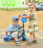 Boy on scooter and girl Stock Photos