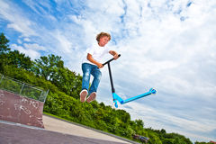 Boy with scooter is going airborne Royalty Free Stock Image