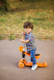 Boy with scooter having fun in the park Stock Photo