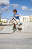 Boy with scooter is jumping at skate park Royalty Free Stock Photos