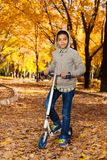 Boy with scooter in October park Royalty Free Stock Photos
