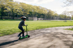Boy on scooter in park Stock Photo
