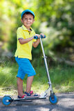 Boy with scooter in the park. Stock Photo