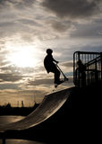 Boy on scooter in skate park jumping on the halfpipe, in mid air. Boy on child's scooter in mid air jump on halfpipe in scate park, sun and sky in background Royalty Free Stock Photography