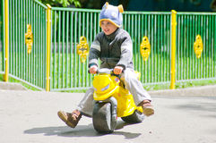 The boy on the scooter. Three year old boy rides on toy scooter. The spring season. He wears a funny hat in the shape of a fish Royalty Free Stock Image