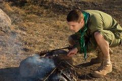 Boy scout blanco Making Fire para cocinar en el campo Foto de archivo libre de regalías