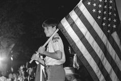 Boy Scout carries the American flag Stock Photo