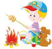 Boy-scout che arrostisce pane su fuoco di accampamento Immagine Stock