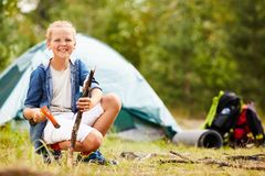 Boy scout. Cheerful boyscout with axe and stick looking at camera while enjoying trip on summer day Stock Photography