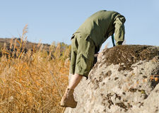 Boy Scout Climbing on a Big Rock at the Field Stock Images