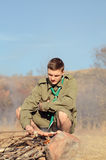 Boy scout Cooking Sausages en el palillo sobre hoguera fotos de archivo libres de regalías