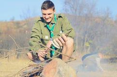 Boy scout Cooking Sausages en el palillo sobre hoguera imagenes de archivo