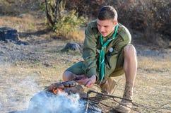 Boy scout Cooking Sausages en los palillos sobre hoguera fotografía de archivo