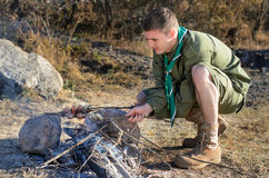 Boy scout Cooking Sausages en los palillos sobre hoguera imágenes de archivo libres de regalías