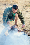 Boy scout Cooking Sausages en los palillos sobre hoguera Imagenes de archivo