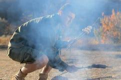 Boy scout Cooking Sausages en los palillos sobre hoguera Fotos de archivo