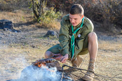 Boy scout Cooking Sausages en los palillos sobre hoguera foto de archivo
