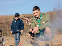 Boy Scout Cooking Sausages on Stick over Campfire Stock Photos