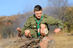 Boy Scout Cooking Sausages on Stick over Campfire Royalty Free Stock Image