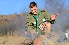 Boy Scout Cooking Sausages on Stick over Campfire Stock Photo