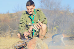 Boy Scout Cooking Sausages on Stick over Campfire Stock Images