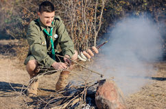 Boy Scout Cooking Sausages on Stick over Campfire Stock Image