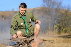 Boy Scout Cooking Sausages on Stick over Campfire Royalty Free Stock Photography