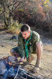 Boy Scout Cooking Sausages on Sticks over Campfire Stock Image