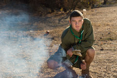 Boy Scout Making Fire on the Campground Stock Photography