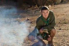 Boy scout Making Fire en el camping Fotografía de archivo